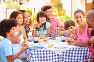 Two Families Eating Meal At Outdoor Restaurant